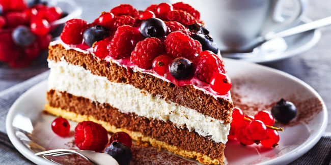 Slice of gourmet fresh berry cake on a plate with layered cream topped with fresh autumn raspberries, blueberries and redcurrants in a close up view on a plate