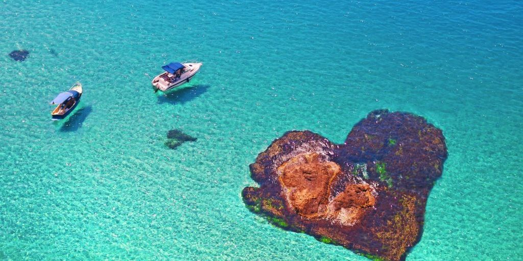 boats floating near the stone in the shape of heart. Romantic island lovers